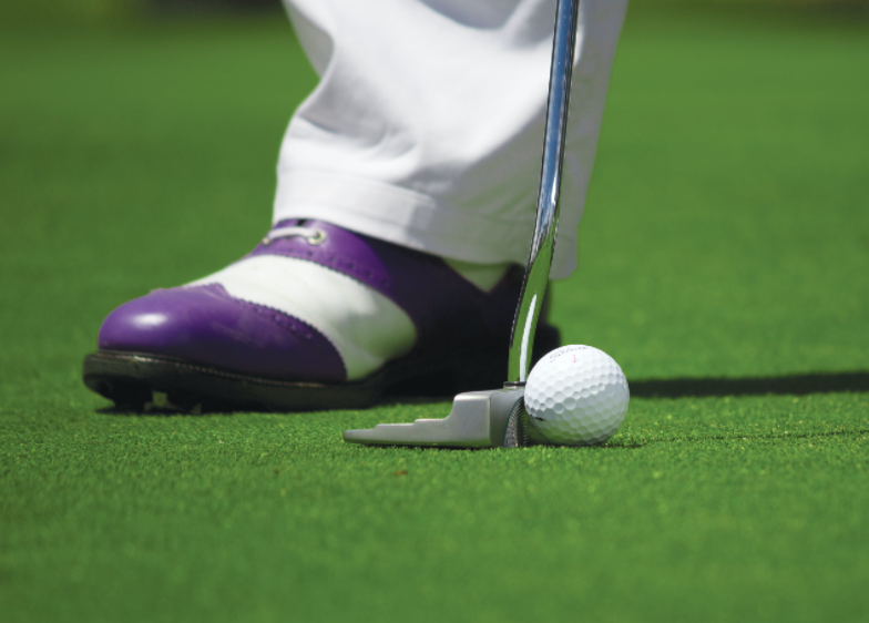 man wearing purple golf shoes hits the ball with a putter